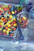 Oven-baked red and yellow cherry tomatoes with olives