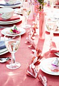 A table laid with a pink tablecloth and a pink paper garland