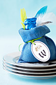A blue chocolate Easter Bunny in bag on a stack of plates