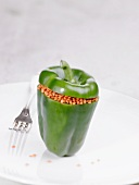 A raw green pepper stuffed with lentils
