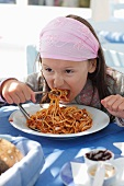 Small girl eating spaghetti bolognese
