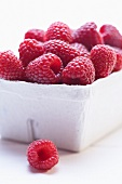Raspberries in cardboard punnet (close-up)