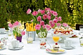 A table set for coffee in a garden with a plate of profiteroles and a vase of pink tulips