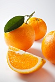 An orange wedge and whole oranges
