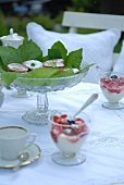 Dessert glasses with a berry and cream dessert; between them, a glass bowl decorated with green leaves, holding small cakes