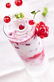 Redcurrants falling into a layered yogurt dessert