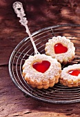 Shortbread biscuits with jam hearts on a wire rack