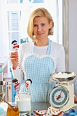 A woman with cake pops and ingredients for Christmas baking