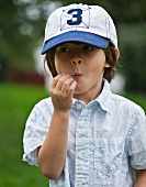 A little boy in a cap chewing