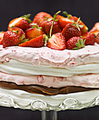 A layered meringue cake with raspberry cream, truffle cream and strawberries
