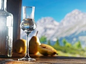 A glass of William's pear schnapps against an alpine backdrop
