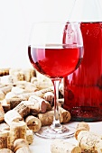 A bottle and a glass of wine and corks