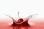 A cherry falling into red juice
