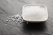 Sea salt in a bowl and on a slate surface