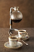 Two cups of coffee and a demijohn (coffee maker) filled with coffee