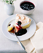 Lemon meringue pie with blackcurrant sauce