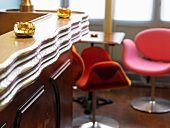 Retro-style hotel bar with brightly-coloured bucket chairs around a small table