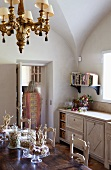 Mix of styles in dining room with chandelier and natural decorative materials