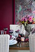 Festlich gedeckter Tisch mit Rotwein und herbstlichem Blumenstrauss