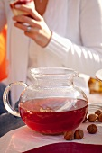 Woman with fruit tea at autumn picnic