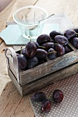 Fresh plums in a wooden crate with an empty glass bowl next to it