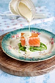 Remoulade being poured over salmon fillet