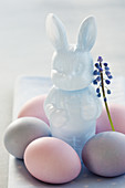 An Easter bunny with a grape hyacinth and pastel-coloured Easter eggs