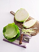 White cabbage, partially sliced, on a chopping board