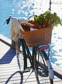 Fresh strawberries and rhubarb in a bicycle basket