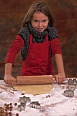 A girl rolling out biscuit dough with a rolling pin on a work surface