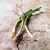 Three spring onions on a wooden surface