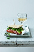 A pastrami, lettuce and herb sandwich with tomato relish