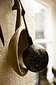 A draining spoon and a wooden ladle hanging on a wall next to a window