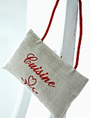 A linen bag embroidered with a words
