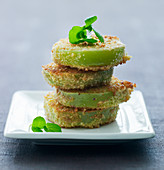 A stack of green breaded tomatoes