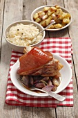 Pork knuckle with shallots, roast potatoes and sauerkraut