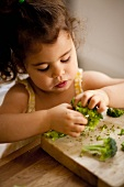 A little girl ripping broccoli