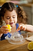 A little girl juicing a lemon