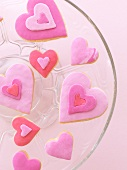 Pink heart-shaped biscuits on a glass plate