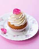 An elegant cupcake decorated with a candied rose petals and silver balls