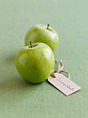 Two Granny Smith apples with a label