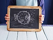 A cartoon fish drawn on a chalkboard