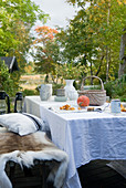 Autumnal table with white table cloth and animal skins on bench in garden