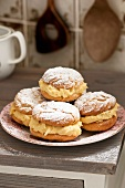 Profiteroles filled with vanilla cream and dusted with icing sugar