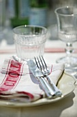 A place setting with a napkin and a drinking glass
