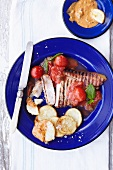 Pork chops with tomatoes, plum sauce and patatas bravas
