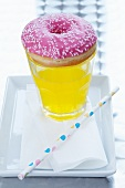 A doughnut on top of a glass of fizzy pop