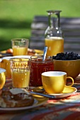 Summer breakfast in the garden with orange juice and jam