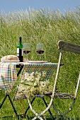 Table with red wine and bread in field