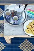 Coffee pot and beakers on tray next to plate of Moroccan flatbread